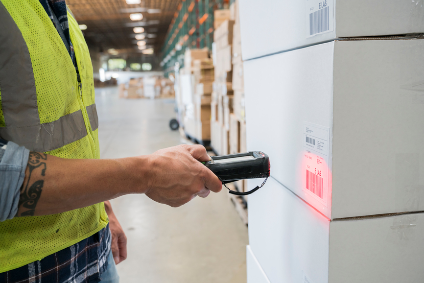 Warehouse worker  wearing a reflective vest and using a hand held RF scanner to check shipping lable bar codes on cardboard boxes full of inventory.