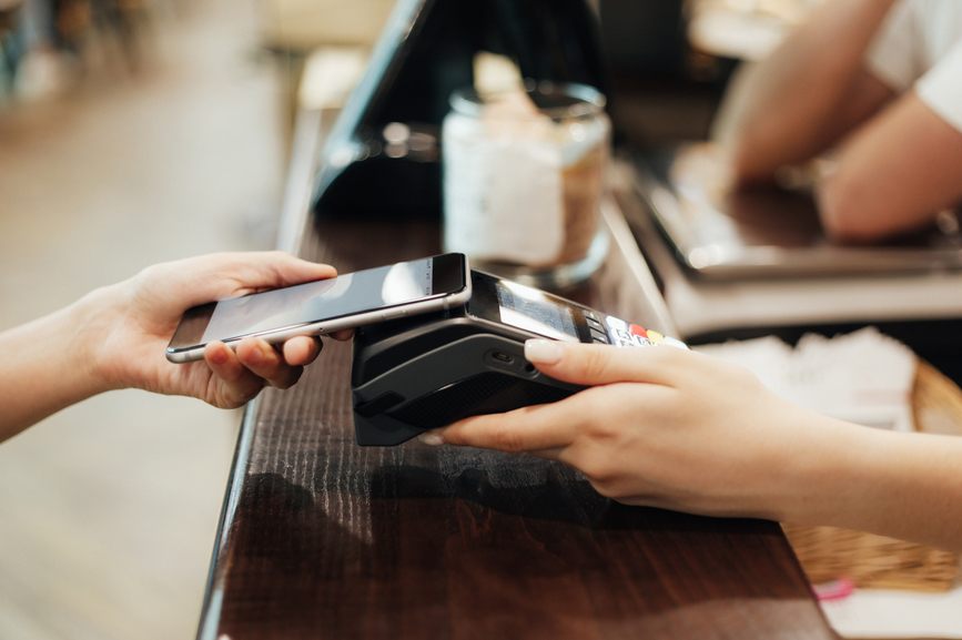 the client pays off at the cash desk through the terminal by phone. close-up